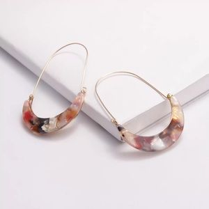 Multi-colored acetate/wire crescent hoop earrings.